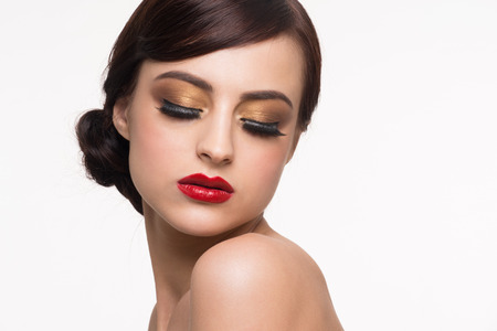 Portrait of young beautiful woman with fashion makeup. Makeup with golden eyeshadow and red lips Stock Photo