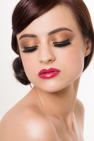 luster: Portrait of young beautiful woman with fashion makeup. Makeup with golden eyeshadow and red lips Stock Photo