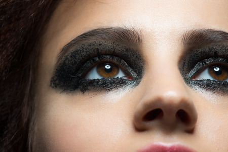 glitter makeup: Closeup image of beautiful woman eye with fashion makeup. Makeup with black glitter. Cosmetic Eyeshadow. Stock Photo