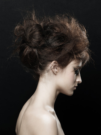 updo: Fashion studio portrait of young beautiful woman with fancy updo hairstyle. Brunette with glamour hairdo. Hair style. Stock Photo