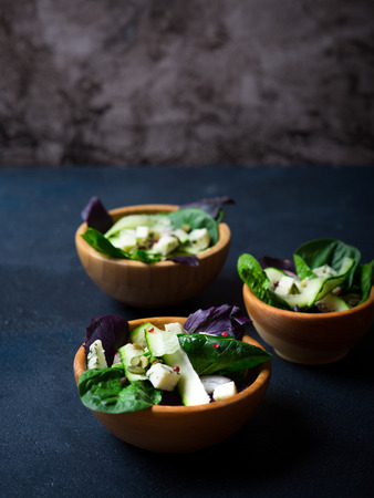 salad bowl: Three healthy vegetable salads with pumpkin seeds in wooden bowls on a dark background