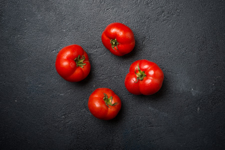 red stone: Ripe red tomatoes on a dark stone background, top view