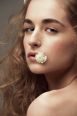 ringlet: Young beautiful woman with perfect healthy skin with flower in her mouth