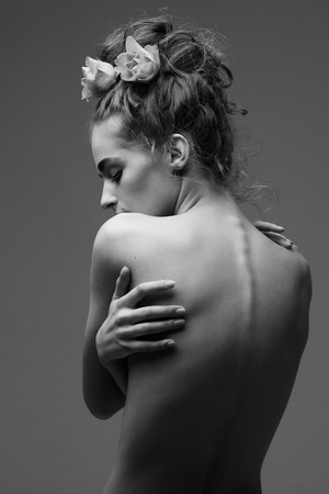 Young beautiful woman with beautiful updo hairstyle hugging herself