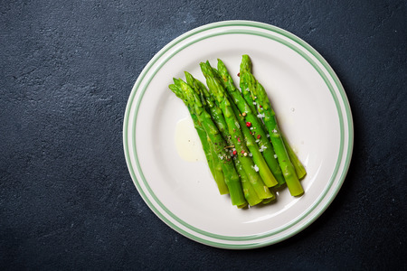 cooked: Cooked asparagus served on a plate over dark  background Stock Photo