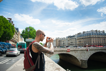photo pictures: Man making a photo of a city using phone.  Male tourist taking pictures on smart phone from bridge on holidays