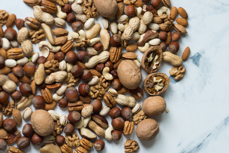 Assorted nuts on white surface Stock Photo