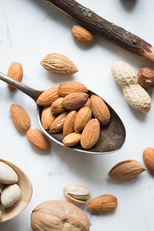 Almond nuts in big spoon over white surface Stock Photo