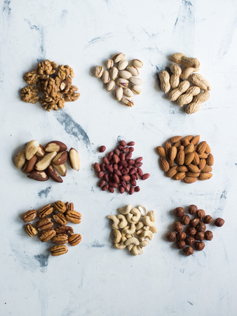 scattering: Assorted nuts on white surface, view from above