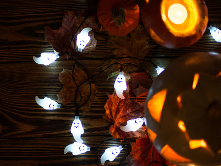 Halloween decorations. Spooky jack-o-lanterns and ghosts burning in darkness Stock Photo