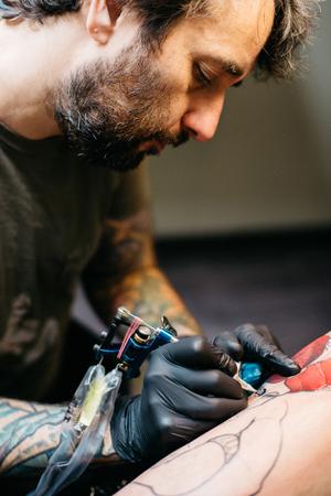 Professional artist making tattoo in salon. Making tattoo with red inks