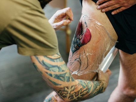Professional artist making tattoo in salon. Close-up view of male hand making tattoo on the leg