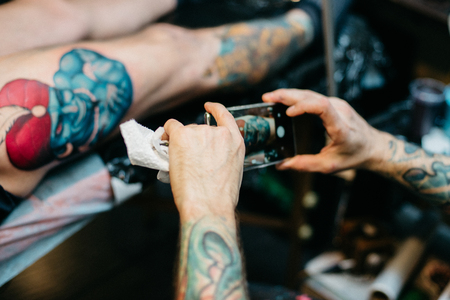 Professional artist making tattoo in salon. Close-up view of tattoo artist making photo of his work with smart phone Stock Photo