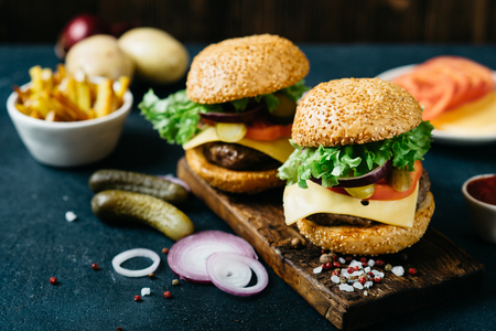Tasty beef burger with lettuce and ripe tomatoes, cheese and red onion. Delicious fresh homemade burger, fastfood concept