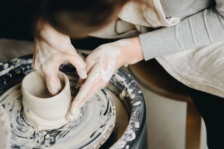 Ceramic working process with clay potters wheel, close-up of female hands. Woman making pottery in studio.