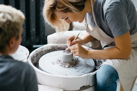 Ceramic working process with clay potters wheel. Young woman making pottery in studio.