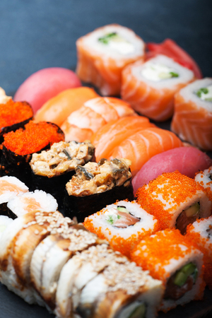 Sushi set. Sushi maki, gunkan and sushi rolls served on stone slate. Japanese food