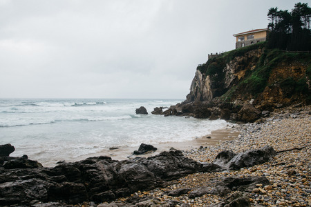 Beautiful beach Playa De Vidiago in a fog weather. Seascape with a house on the hill, Asturias, Northen Spain.