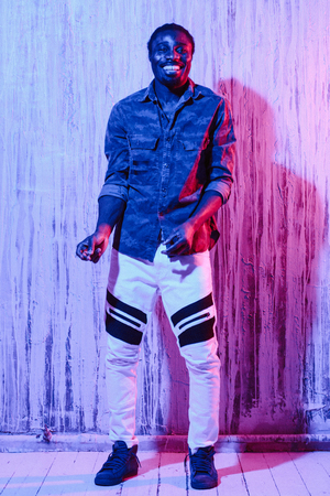 African-American male standing near wall snapping with fingers smiling and looking at camera on colorful neon illumination