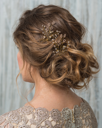Portrait of pretty woman with beautiful hairstyle decorated by gold shiny hair accessory, rear view
