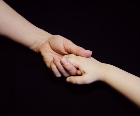 Anya ad kezét a gyermek a fekete háttér, Hands, családi Stock fotó