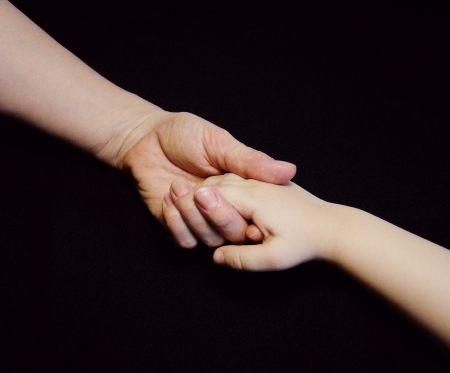 Mother giving hand to a child on black background, Hands, Family  Foto de archivo