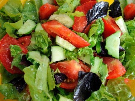 Background of salad leaves, tomatoes, cucumbers and basil leaves  Macro photo of a delicious salad