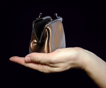Female hand holds an empty change purse on black background  Asking for help