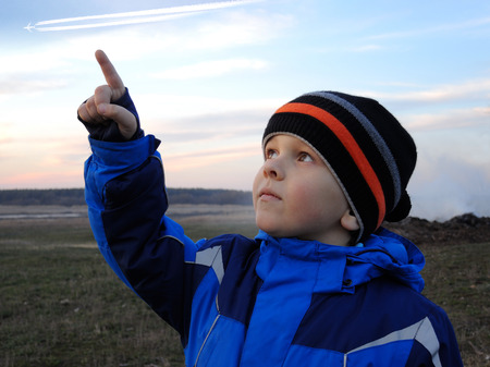 Boy looking into the sky, shows hand and looks aside