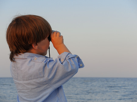 The boy looks in the field-glass at a sea            Foto de archivo