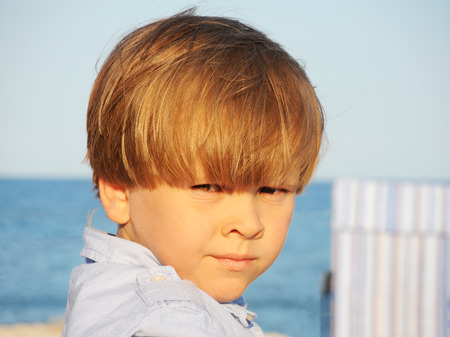 Portrait of an adorable little boy on a background of the sea, in the rays of the setting sun.