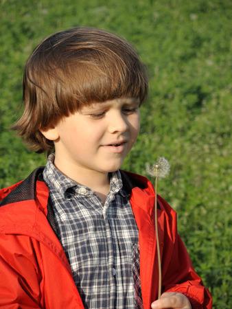 boy beautiful: Beautiful little boy blowing dandelion. Happiness, fashionable concept.