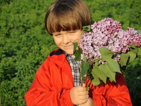Portrait of a smiling young boy standing in the forest field meadow with lilac purple flowers in his hands. Happiness, fashionable concept. Lifestyle. Happy child with bouquet of flowers. Mothers day concept.
