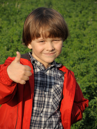 Portrait of a smiling young boy gesturing thumbs on the nature. Happiness, fashionable concept. Lifestyle.