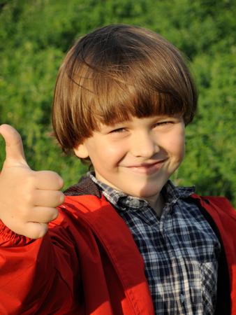 Portré, mosolygós fiatal fiú intett hüvelykujját a természet. Boldogság, divatos fogalom. Életmód.