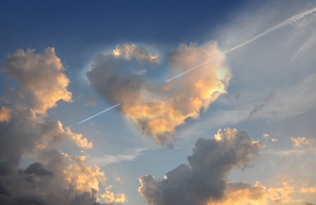 Love is in the air. Burning heart. Fluffy cloud of the shape of heart, on a deep blue sky.