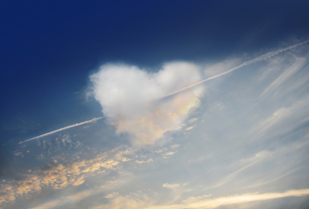 Love is in the air. Fluffy cloud of the shape of heart, on a deep blue sky.