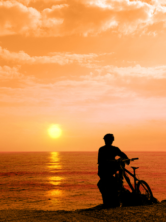 Boy with his bicycle resting and looking at the sea. Silhouette boy with his bicycle during sunset. Man with his bicycle outdoors by the sea against sunset. Summer. Foto de archivo