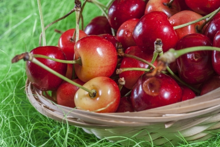 macrophotography: Close up picture of basket of red cherries on a green backgrund Stock Photo