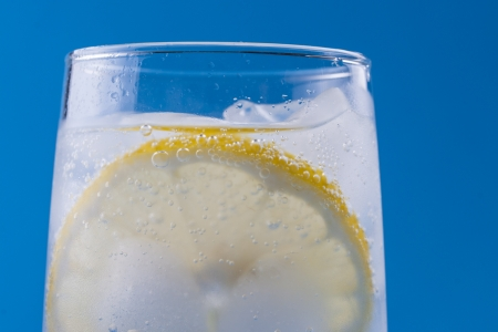 Summer fresh drink - cold sparkling water in a glass with some ice and slice of a lemon over a solid blue background  photo