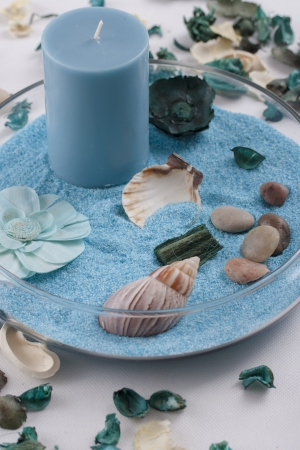 excersise: Aromatherapy - blue candle and dried leafs over a blue sand Stock Photo