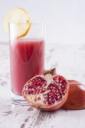 Homemade fresh squeezed glass of pomegranate juice on a bright wooden background Stock Photo