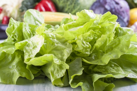 solid blue background: Close up photo of a green salad on a solid wooden light blue background