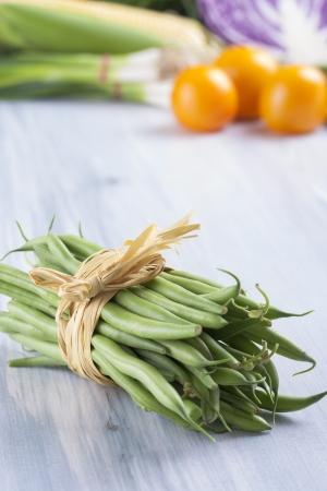 Close up photo of edible vegetables - a green bean with some vegetables in the background on a solid light blue wooden table photo