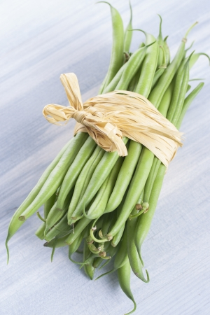 snap bean: Close up photo of edible vegetables - a green bean on a solid light blue wooden table