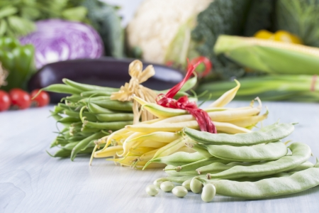 vax: Close up photo of edible vegetables - a green and yellow vax beans with some vegetables in the background on a solid light blue wooden table Stock Photo