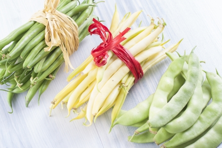 vax: Close up photo of edible vegetables - a green and yellow vax beans on a solid light blue wooden table