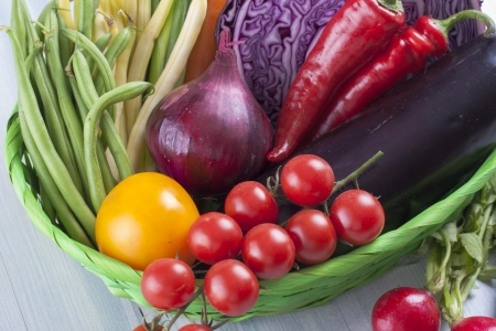 Edible plants composition - colorful fresh vegetables siting in a brown basket on a solid blue wooden background photo