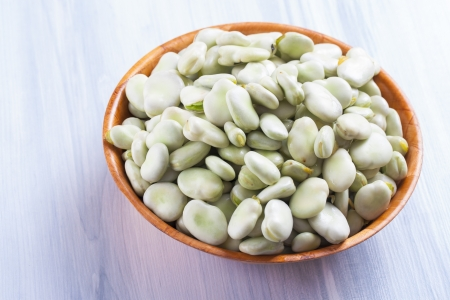 bakla: Close up photo of edible vegetables - a broad bean on a solid  bright blue wooden table