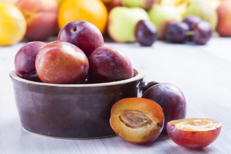 Close up photo of edible fruits - a plums with other full colors fruits in the background on a solid  bright blue wooden table photo
